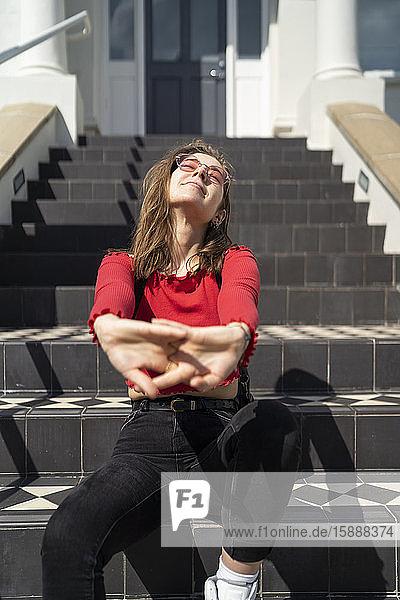 Junge Frau sitzt bei Sonnenschein auf der Treppe am Hauseingang Junge Frau sitzt bei Sonnenschein auf der Treppe am Hauseingang