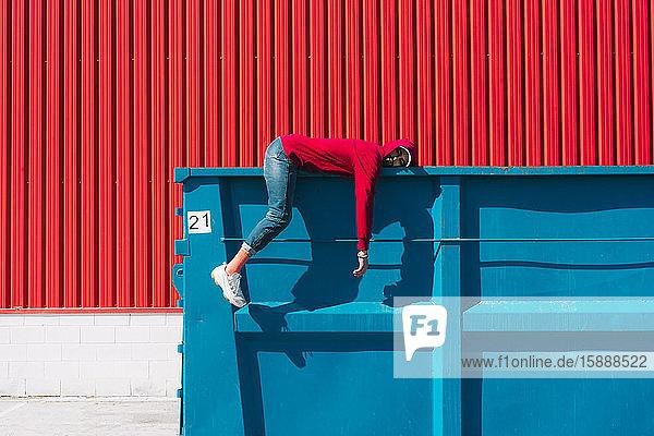 Junger Mann mit roter Kapuzenjacke auf dem Rand des Containers liegend