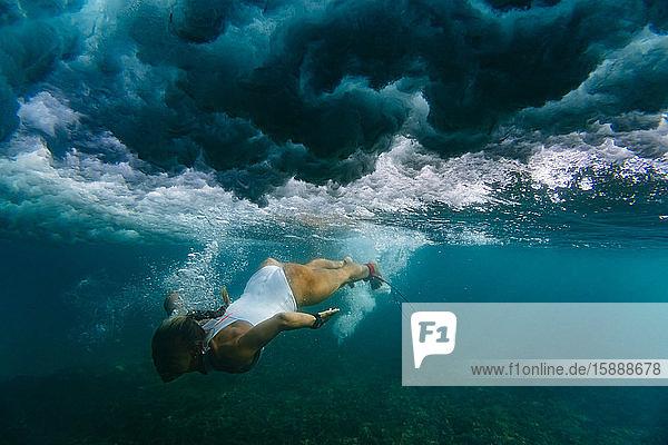 Indonesien  Unterwasseransicht einer erwachsenen Frau beim Tauchen im Meer
