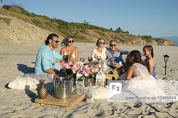 Family and friends enjoying picnic while sitting at beach against blue sky during sunset. Riviera Nayarit  Mexico