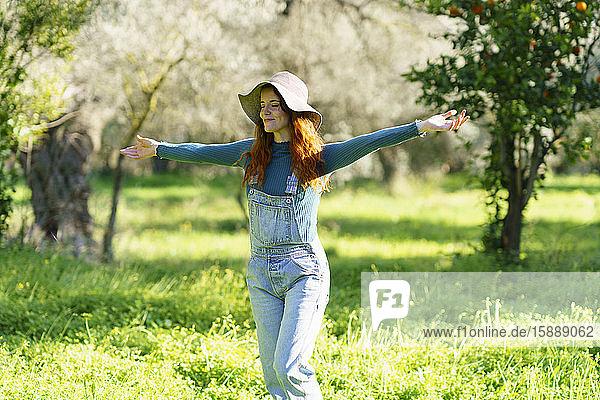 Rothaarige Frau mit Hut  die mit offenen Armen die Landschaft genießt
