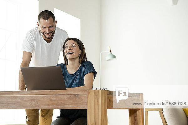 Glückliches Paar arbeitet von zu Hause am Laptop im Home-Office im modernen Wohnzimmer