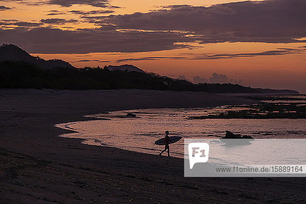 Indonesia  Sumbawa  Silhouette of female surfer at late dusk