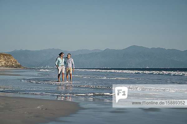 Mature gay men holding hands while walking on shore at beach against clear blue sky  Riviera Nayarit  Mexico