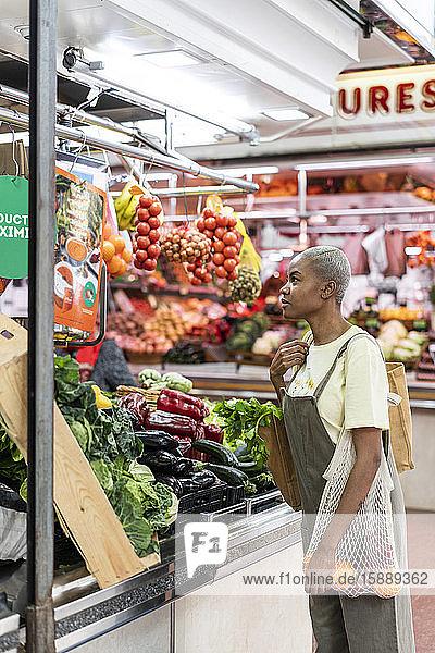 Frau kauft Lebensmittel in einer Markthalle Frau kauft Lebensmittel in einer Markthalle