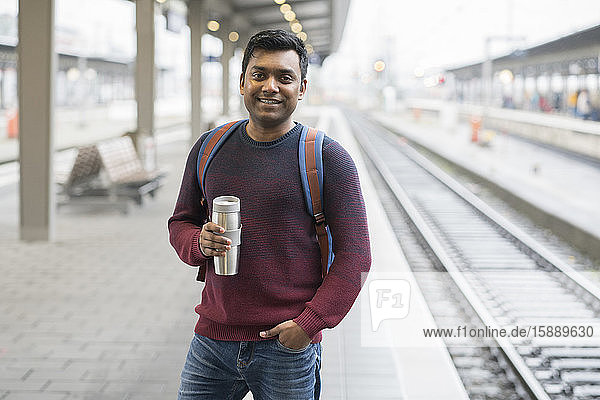 Portrait of smiling man holding reusable cup at the train station