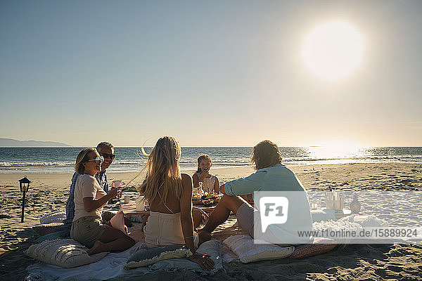 Ältere männliche und weibliche Freunde mit einem Mädchen  die bei Sonnenuntergang am Strand ein Picknick gegen den Himmel genießen. Riviera Nayarit  Mexiko