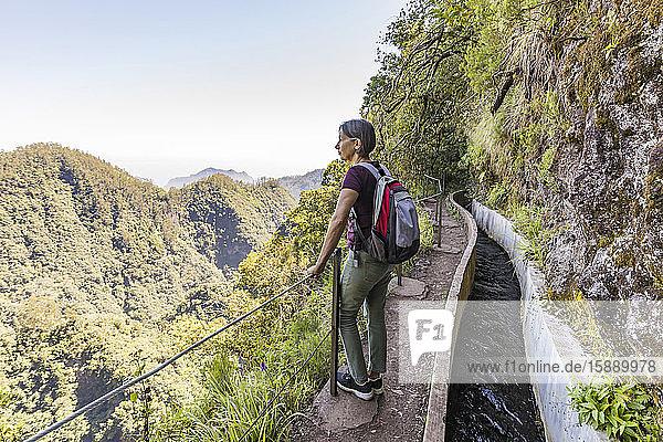 Portugal  Madeira  Ribeiro Frio  Rucksacktouristin bewundert die umliegende Landschaft vom Aussichtspunkt entlang der Levada do Furado