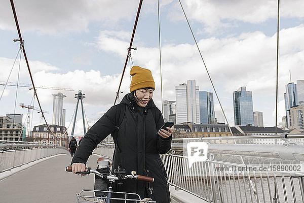 Lächelnde Frau mit Fahrrad mit Smartphone auf einer Brücke  Frankfurt  Deutschland
