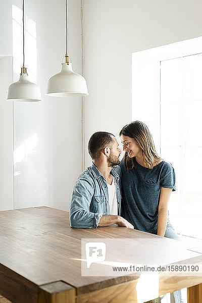 Zärtliches verliebtes Paar  das sich zu Hause entspannt und am Tisch sitzt