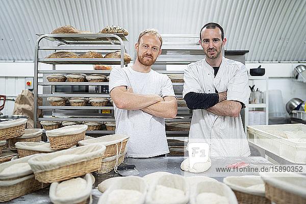 Porträt von zwei selbstbewussten Bäckern in einer Bäckerei Porträt von zwei selbstbewussten Bäckern in einer Bäckerei