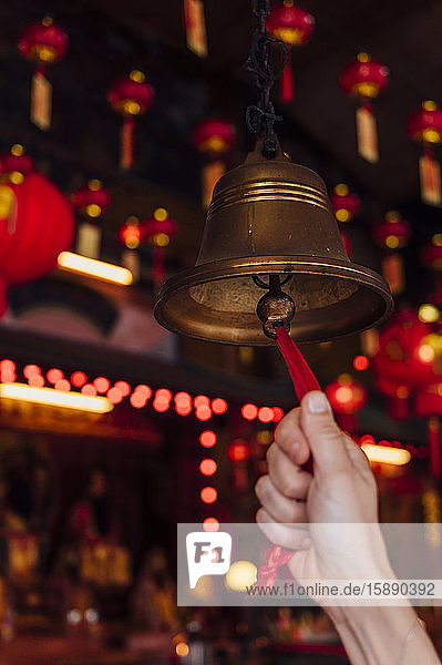 Malaysia  Hand of woman ringing small bell inside temple