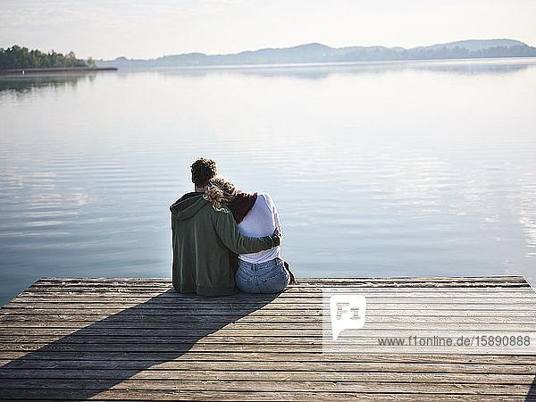 Romantisches Paar sitzt auf einem Steg am See