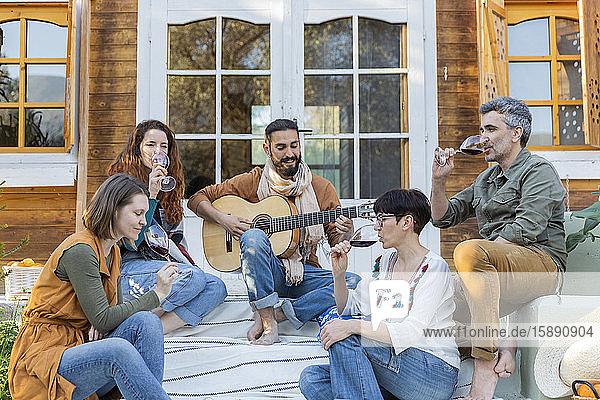 Freunde spielen Musik auf der Gitarre und trinken Wein vor einer Hütte auf dem Land