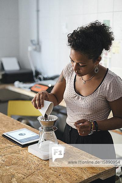 Frau  die in einer Kaffeerösterei arbeitet und frischen Filterkaffee zubereitet