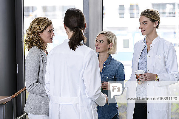 Businesswoman and female doctors talking in hospital