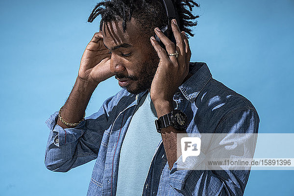 Portrait of stylish young man listening to music with headphones