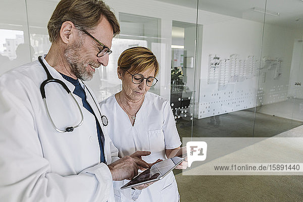 Doctor and assistant using tablet in medical practice
