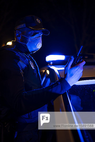 Policeman on emergency mission  wearing face mask  holding phone