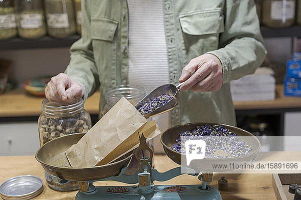 Nahaufnahme eines älteren Mannes hinter der Ladentheke in seinem Geschäft  der getrocknete Lavendelblüten in eine Papiertüte gießt Nahaufnahme eines älteren Mannes hinter der Ladentheke in seinem Geschäft, der getrocknete Lavendelblüten in eine Papiertüte gießt