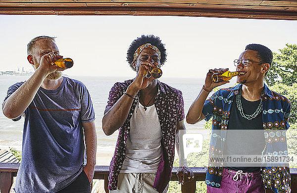 Multi-ethnische männliche Freunde trinken Bier  während sie auf dem Balkon stehen