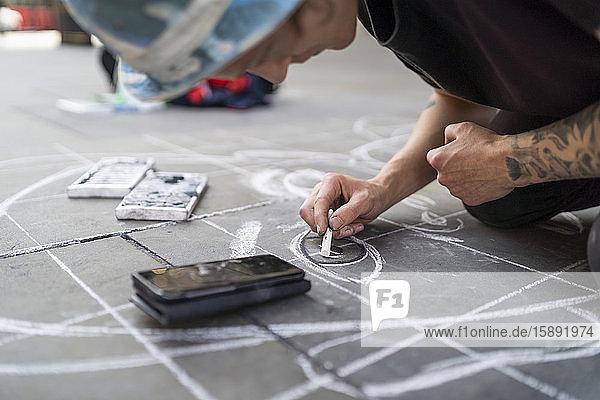 Straßenkunst  Bürgersteigkünstler  der ein Auge auf den Bürgersteig wirft und ein Smartphone benutzt Straßenkunst, Bürgersteigkünstler, der ein Auge auf den Bürgersteig wirft und ein Smartphone benutzt