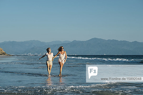Full length of carefree mature lesbians walking on shore at beach against clear blue sky  Riviera Nayarit  Mexico