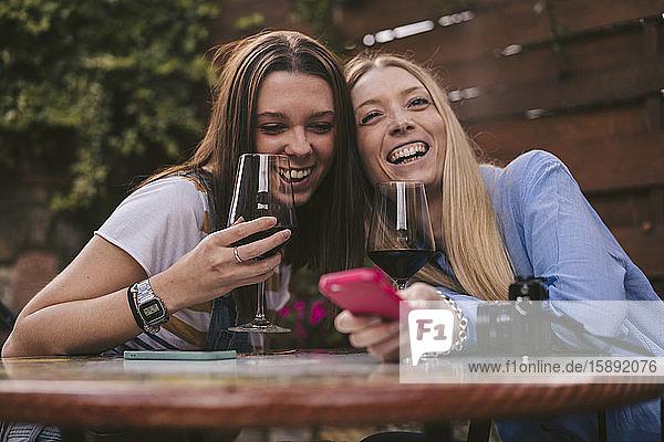 Porträt von zwei glücklichen Frauen bei einem Glas Rotwein im Freien Porträt von zwei glücklichen Frauen bei einem Glas Rotwein im Freien