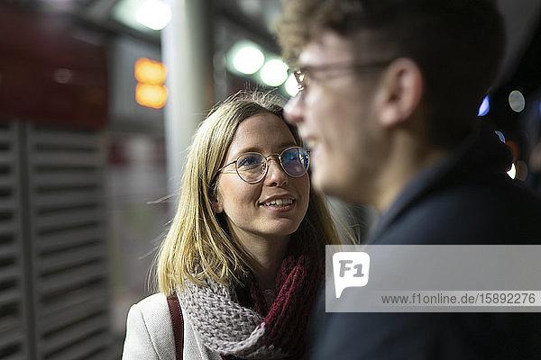 Porträt einer lächelnden jungen Frau  die ihren Freund anschaut
