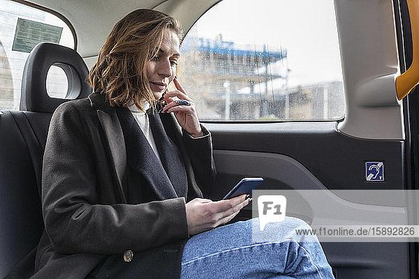 Geschäftsfrau auf dem Rücksitz eines Taxis mit Blick auf das Telefon
