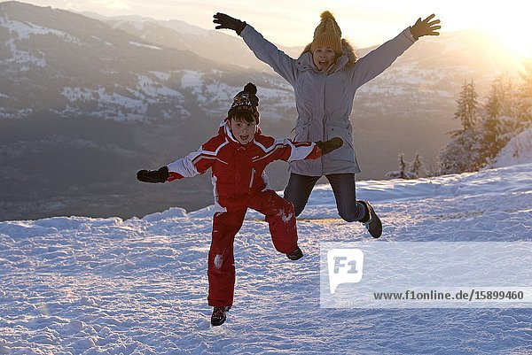 Boy and mother jumping on snow.