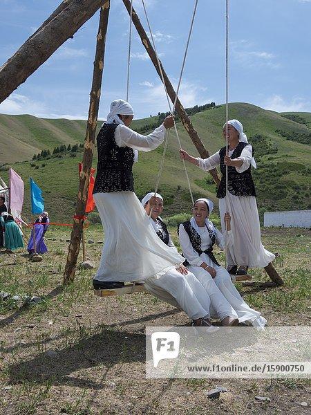 Woman in traditional garb having fun on a swing. Folk Festival commemorating the origin myth the Tien Shan Maral (Tian Shan wapiti)  an origin myth of the Kyrgyz tribes. Near Tasch Baschat  Naryn region. Asia  Central Aisa  Kyrgyzstan