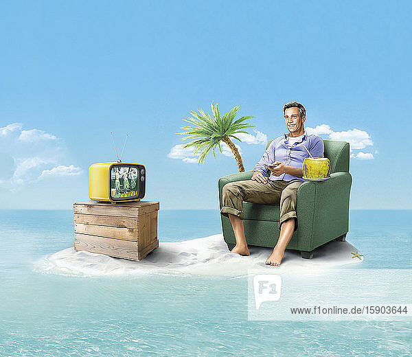 Happy man stranded on desert island watching television