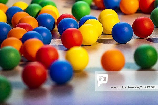 Lot of colorful balls on the floor.