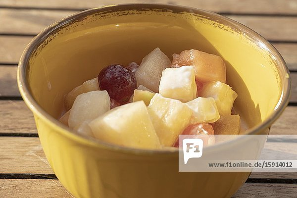 Top view of white bowl full of fruit salad containing strawberries  grapes  orange  kiwi  pineapple and apple.