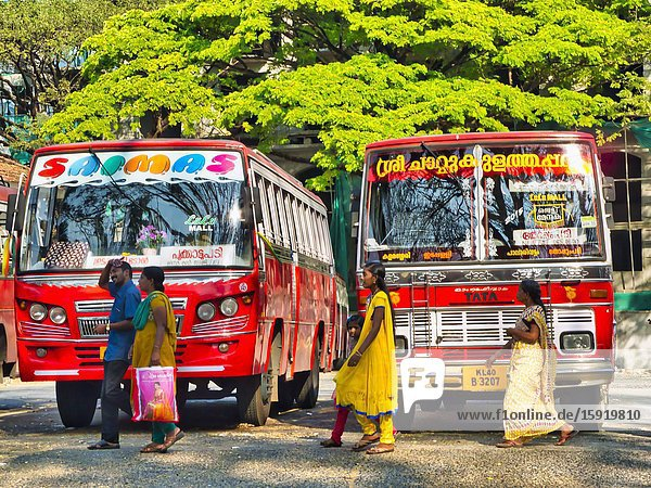 People walking in front of two red buses  Fort Cochin  Fort Kochi  Kerala  India.