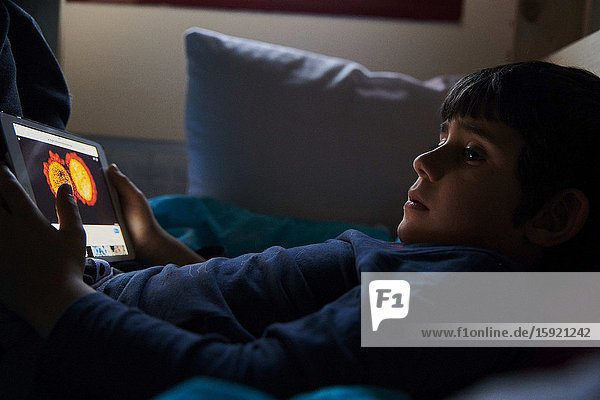 A little boy watches a image of coronatavirus in his iPad on the bed in his room due to the corona crisis. The Spanish government ordered all schools and public places to be closed until further notice in attempt to control the spread of the COVID-19 Coronavirus.