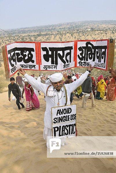 India  Rajasthan  Mukam  Samrathal Dora   Jambeshwar festival  Bishnoi activist holding signs among walking pilgrims against the use of plastic.