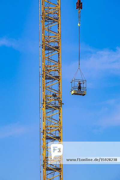 Construction worker hoisted up at a construction site at Strijp-S  Eindhoven  The Netherlands.