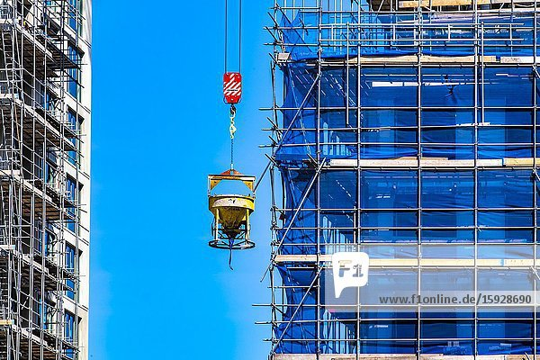 Cement mixer machine being lifted at a construction site at Strijp-S  Eindhoven  The Netherlands.