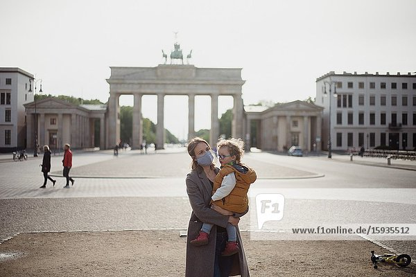 Mother and son walking with mask in Berlin in an empty Brandenburg gate during Corona time.