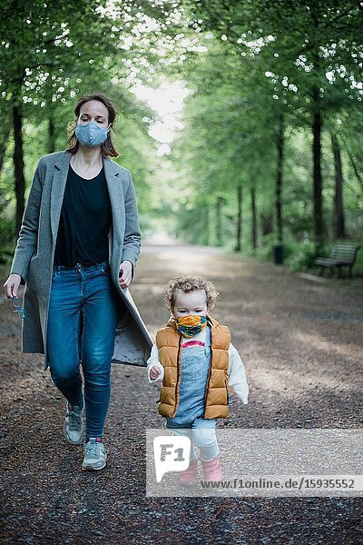 Mother and son walking in the park with mask during corona time.
