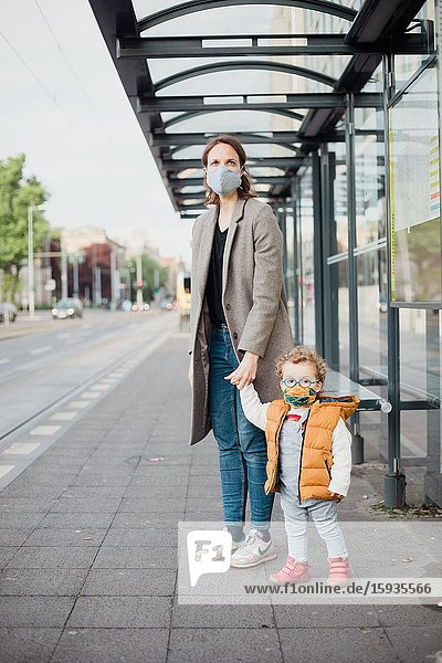 Mother and son with mask waiting for the bus.