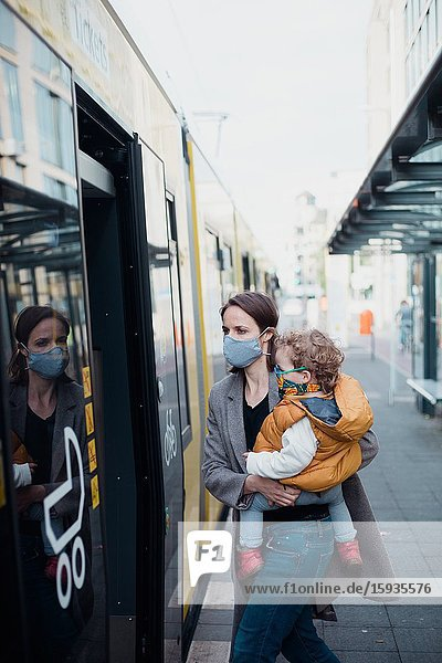 Mother and son taking public transport with mask during corona days.