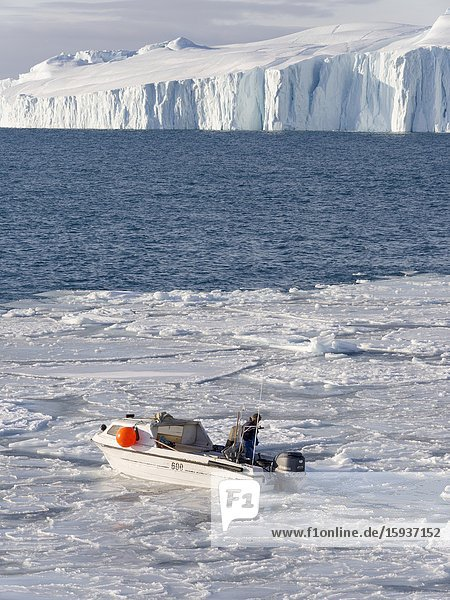 Fisherman fishing in the fjord. Winter at the Ilulissat Icefjord  located in the Disko Bay in West Greenland  the Icefjord is part of the UNESCO world heritage. America  North America  Greenland  Denmark.