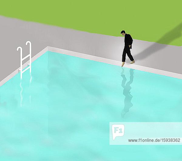 Businessman putting toe in swimming pool water