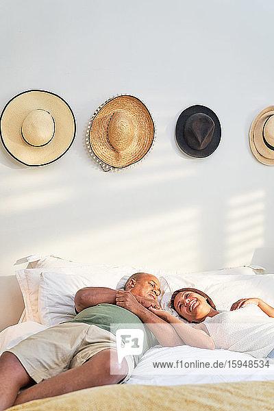 Glückliches  liebevolles Paar  das sich im Bett entspannt und unterhält