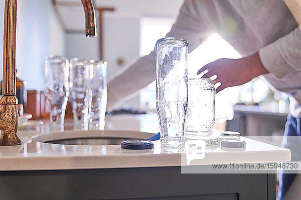 Mann wäscht Glasflaschen an der Küchenspüle Mann wäscht Glasflaschen an der Küchenspüle