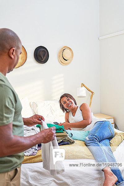 Sprechendes Paar und zusammenklappbare Wäsche im Schlafzimmer