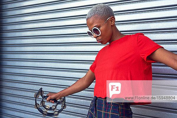 Coole junge Frau spielt Tamburin vor der Garage